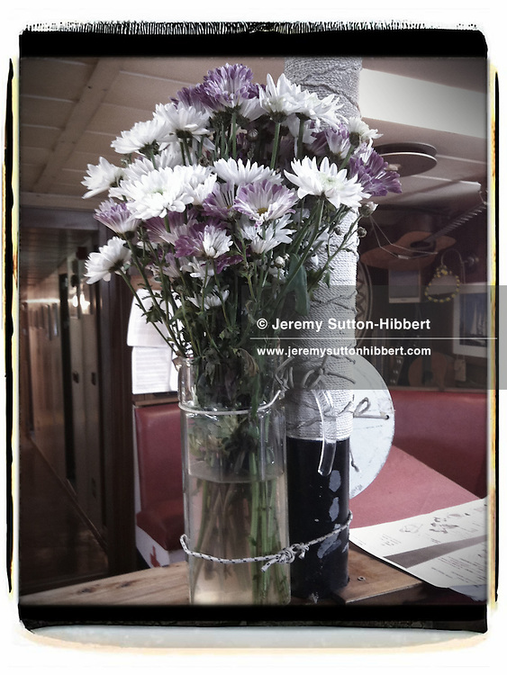 Flowers tied to pole (so as not to fall over at sea), in the mess room, on the Greenpeace ship Rainbow Warrior, as it sails to Fukushima in Japan, on Tuesday 26th April 2011.
