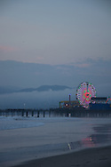 Dusk at the Santa Monica Pier.  Photo taken from the beach looking out to the ferris wheel with the cloud covered Santa Monica Mountains behind. Santa Monica, CA 2.1.15