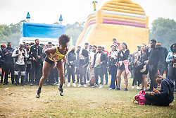 © Licensed to London News Pictures . 12/08/2018. Manchester , UK . Festival-goers dance in front of a stage . The second day of the annual Caribbean Carnival in Alexandra Park in Moss Side , celebrating music , food and Afro-Caribbean culture . A nearby shooting overnight lead to at least ten people injured . Ten people are in hospital . Photo credit : Joel Goodman/LNP