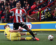 Sid Nelson fouling Andre Grey during the Sky Bet Championship match between Brentford and Millwall at Griffin Park, London, England on 21 March 2015. Photo by Matthew Redman.