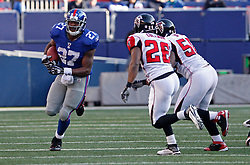 Nov 22, 2009; East Rutherford, NJ, USA; New York Giants running back Brandon Jacobs (27) runs with the ball while Atlanta Falcons safety Erik Coleman (26) tries to tackle him during the first half at Giants Stadium. Mandatory Credit: Ed Mulholland