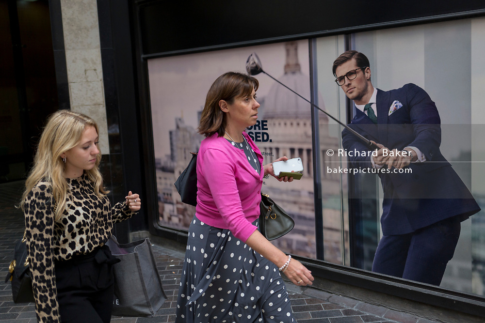 Women walk past a closed shop poster featuring a businessman wearing a blue suit - a favoured style and colour of menswear in the City of London, the capital's financial district - aka the Square Mile, on 29th August 2018, in London, England.