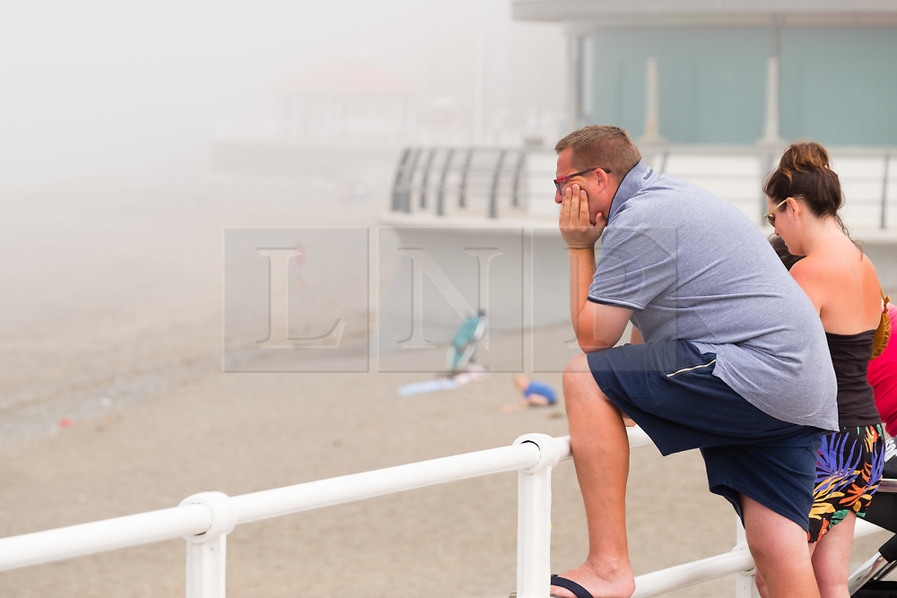 © Licenced to London News Pictures<br /> Aberystwyth,UK. 8/07/2018. A man looks over the beach on a  misty morning in Aberystwyth, as the sea mist rolls in off Cardigan Bay to take the edge off the temperatures on the west wales coast. <br /> Over much of the UK  the prolonged  heat wave and very dry weather continues unbroken, with temperatures expected to climb again towards the end of the week. Photo credit Keith Morris/LNP