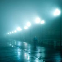 Figure walking on a wet foggy night.