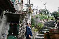 """PISCIOTTA, ITALY - 22 APRIL 2018: Donatella Marino, owner of the """"Alici di Menaica"""" store and processing workshop, walks up the stairs to go to Sunday mass in Pisciotta, Italy, on April 22nd 2018.<br /> <br /> Former restaurant owners Donatella Marino and her husband Vittorio Rimbaldo have spent the recent years preparing and selling salted anchovies, called alici di menaica, to a growing market thanks to a boost in visibility from the non-profit Slow Food.  The ancient Menaica technique is named after the nets they use brought by the Greeks wherever they settled in the Mediterranean. Their process epitomizes the concept of slow food, and involves a nightly excursion with the special, loose nets that are built to catch only the larger swimmers. The fresh, red anchovies are immediately cleaned and brined seaside, then placed in terracotta pots in between layers of salt, to rest for three months before they're aged to perfection.While modern law requires them to use PVC containers for preserving, the government recently granted them permission to use up to 10 chestnut wood barrels for salting in the traditional manner. The barrels are """"washed"""" in the sea for 2-3 days before they're packed with anchovies and sea salt and set aside to cure for 90 days. The alici are then sold in round terracotta containers, evoking the traditional vessels that families once used to preserve their personal supply.<br /> <br /> Unlike conventional nets with holes of about one centimeter, the menaica, with holes of about one and half centimeters, lets smaller anchovies easily swim through. The point may be to concentrate on bigger specimens, but the net also prevents overfishing."""