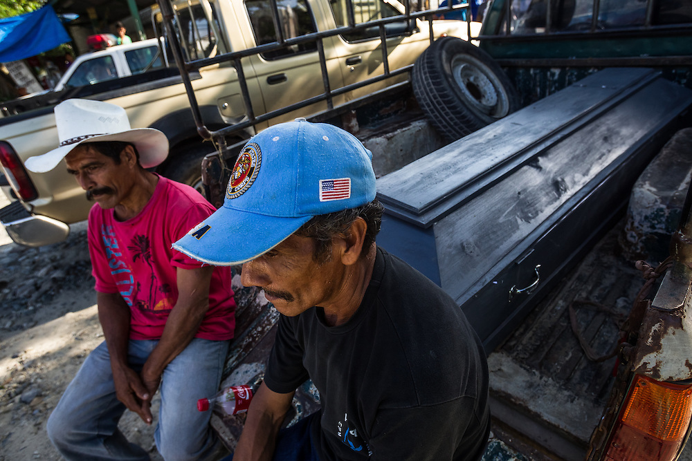 "SAN PEDRO SULA, HONDURAS - MAY 25, 2014:  Family members wait outside of the San Pedro Sula morgue on the back of a pickup truck holding a wooden coffin, to receive the body of a  farmer shot five times in the head.  His family said it was likely he was killed for not paying local gangs a monthly ""War Tax"" they collect from residents. The morgue was overflowing, with over 60 corpses, all from gunshots or other violent deaths, over a period of two days. Staff at the morgue reported regularly receiving corpses of children under ten years old that had been shot point-blank.  They described a two-year old shot multiple times in the skull, and a four-year old girl that had her arms and legs chopped of with a machette. A surge in violence in Honduras  is what could be one of the causes of a boom of child migrants arriving in the United States in recent months. PHOTO: Meridith Kohut for The New York Times"