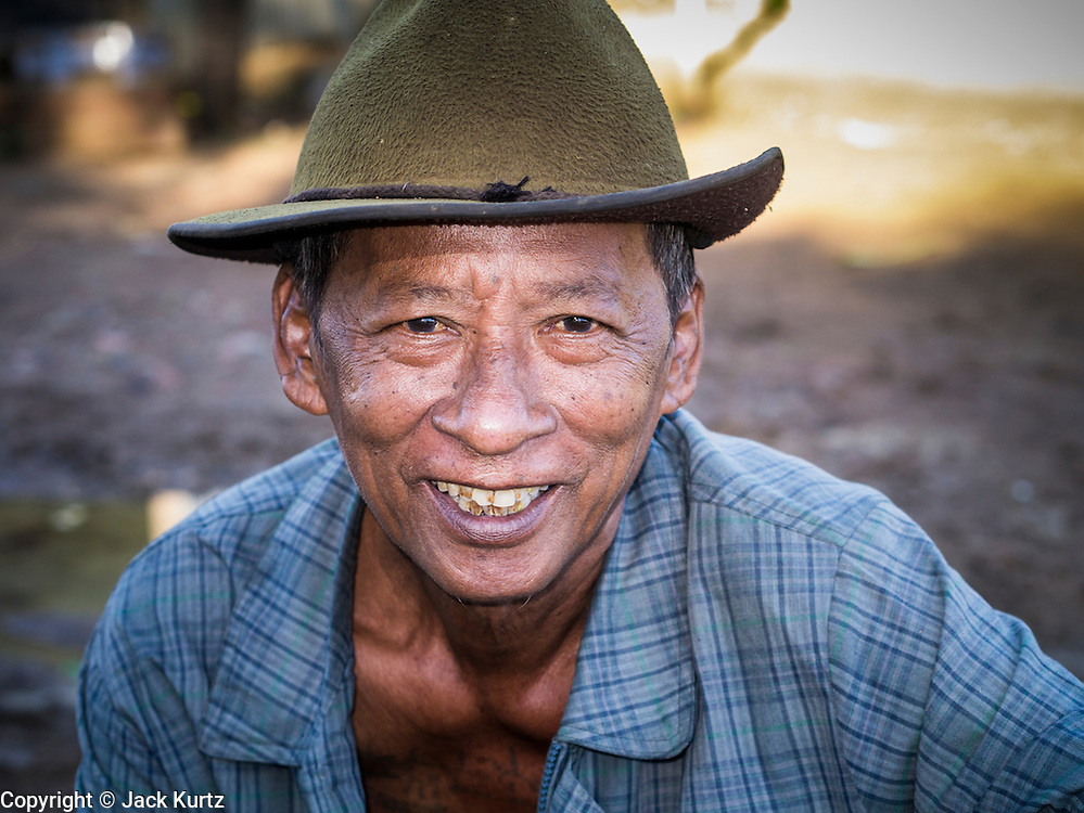 29 JUNE 2013 - BATTAMBANG, CAMBODIA:  Portrait of a man who drives a bamboo train. The bamboo train, called a norry (nori) in Khmer is a 3m-long wood frame, covered lengthwise with slats made of ultra-light bamboo, that rests on two barbell-like bogies, the aft one connected by fan belts to a 6HP gasoline engine. The train runs on tracks originally laid by the French when Cambodia was a French colony. Years of war and neglect have made the tracks unsafe for regular trains.  Cambodians put 10 or 15 people on each one or up to three tonnes of rice and supplies. They cruise at about 15km/h. The Bamboo Train is very popular with tourists and now most of the trains around Battambang will only take tourists, who will pay a lot more than Cambodians can, to ride the train.       PHOTO BY JACK KURTZ
