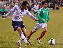United States forward Brian Ching (11) sends a cross past Mexico midfielder Israel Martinez (14).  The United States men's soccer team defeated the Mexican national team 2-0 in CONCACAF final group qualifying for the 2010 World Cup at Columbus Crew Stadium in Columbus, Ohio on February 11, 2009.