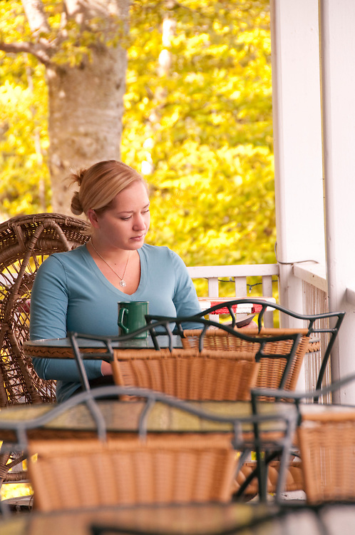 A young woman reads a book at Chamberlin's Ole Forest Inn on Big Manistique Lake near Curtis Michigan in autumn.