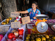 31 DECEMBER 2015 - BANGKOK, THAILAND: A fruit vendor in front of a now closed shop in Bang Chak Market. The market is supposed to close permanently on Dec 31, 2015. The Bang Chak Market serves the community around Sois 91-97 on Sukhumvit Road in the Bangkok suburbs. About half of the market has been torn down. Bangkok city authorities put up notices in late November that the market would be closed by January 1, 2016 and redevelopment would start shortly after that. Market vendors said condominiums are being built on the land.          PHOTO BY JACK KURTZ