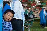 24 APRIL 2005 - SAN CRISTOBAL DE LAS CASAS, CHIAPAS, MEXICO: A Mayan Indian boy peers out from behind his mother during a Catholic mass in an indigenous church. The Catholic church in Chiapas is under increasing pressure and facing competition from evangelical Protestant churches in Mexico.  PHOTO BY JACK KURTZ