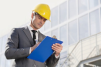Young male architect writing on clipboard against office building