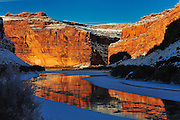 The red rock of the canyon walls reflects into the icy Colorado River.