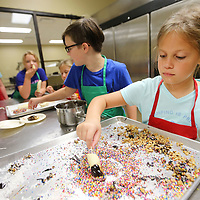 Olivia Robertson, 9, of Tupelo, dips her Banana Pop into at tray of toppings after coating the top with chocolate as part of a cooking exercising during her time in the Culinary Camp Thursday afternoon at the ICC Belden Campus.