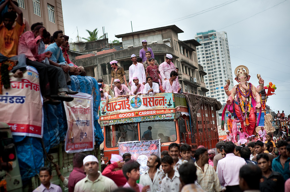A huge idol of lord Ganesh being paraded on the streets of Mumbai, while other trucks carry smaller idols and family members on the way for immersion of the idols in the Indian ocean on the last day of the Ganesh Chaturthi festival. Ganesh, the elephant-headed son of Shiva and Parvati is widely worshiped as the supreme God of wisdom, prosperity and good fortune. Mumbai, September 2009.