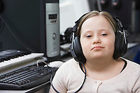 Portrait of girl (10-12) with Down syndrome wearing headphones in home recording studio