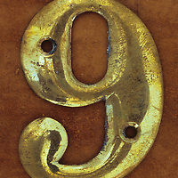 Slightly tarnished brass screw-on house number 9 or 6 lying on brown metal surface