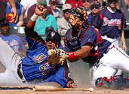 The New York Mets' Aarom Baldiris, left, beats the tag of Atlanta Braves catcher Brayan Pena during the sixth inning of their Spring Training game in Lake Buena Vista, Florida.