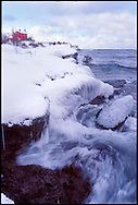 THE WATERS OF LAKE SUPERIOR SWIRL AROUND THE ROCKY COAST OF MARQUETTE MICHIGAN NEAR THE MARQUETTE LIGHTHOUSE IN WINTER.