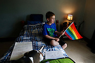 Bryan Brown, 10, holds a pride flag in his bedroom Tuesday, June 28, 2016, at his home in Orient, Iowa. Bryan, who was born a girl, told his mother he felt like a boy at an early age. The rural Iowa fifth-grader is now living his life as a boy at home and school, and his mother is considering hormone blockers before Bryan hits puberty.