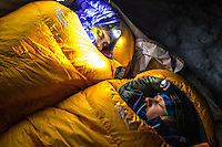 Two female mountaineers sleep up in down-insulated bags on a cold winter night in Mont Blanc Massif.