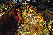 A young boy stands by the candlelit gravesite of a family member during the Day of the Dead festival October 31, 2017 in Tzintzuntzan, Michoacan, Mexico.
