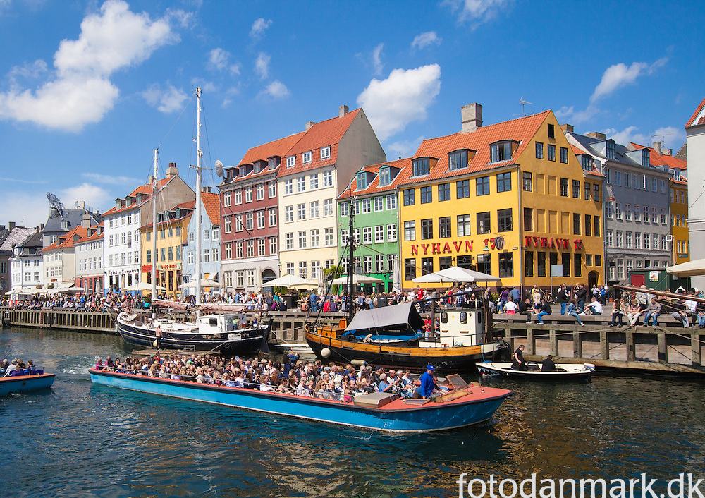"""Nyhavn (Danish pronunciation: [ˈnyhɑʊ̯n]) is a 17th century waterfront, canal and entertainment district in Copenhagen, Denmark. Stretching from Kongens Nytorv to the harbour front just south of the Royal Playhouse, it is lined by brightly coloured 17th and early 18th century townhouses and bars, cafes and restaurants. Serving as a """"heritage harbour"""", the canal has many historical wooden ships. Nyhavn was constructed by King Christian V from 1670-73, maybe dug by Swedish war prisoners from the Dano-Swedish War 1658-60. It is a gateway from the sea to the old inner city at Kongens Nytorv (King's Square), where ships handled cargo and fishermens' catch. It was notorious for beer, sailors, and prostitution. Danish author Hans Christian Andersen lived at Nyhavn 18 for some years."""