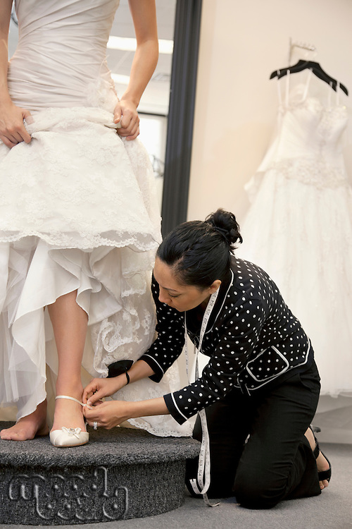 Mature female employee helping bride with footwear in bridal boutique