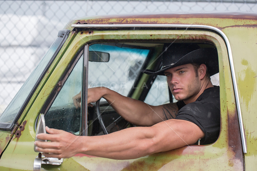 masculine cowboy sitting in an old pick up truck