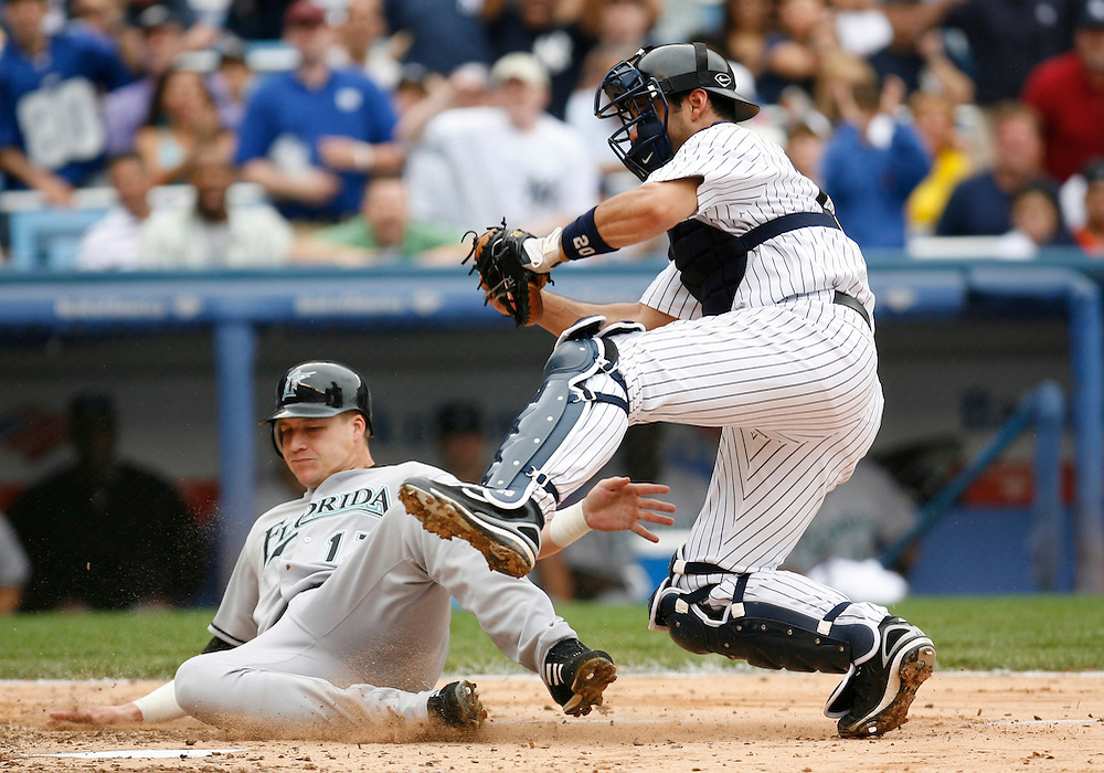 Jorge Posada of the New York Yankee's tags Mike Jacobs of the Florida Marlins out at the plate in the 3rd inning at Yankee Stadium, Bronx, New York, Sunday 25 June 2006. (Andrew Gombert for the New York Times)