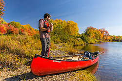 A man and his canoe on the East Branch of the Penobscot River in Maine's Northern Forest. Fall.