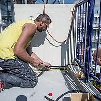 Nederland, Amsterdam, 30 augustus 2016.<br /> Dak en gevelwerkzaamheden bij panden in de straten Warnsborn en Spelderholt in Amsterdam Noord.<br /> Op de foto: Het voegen van de naden van balkons.<br /> <br /> <br /> Foto: Jean-Pierre Jans