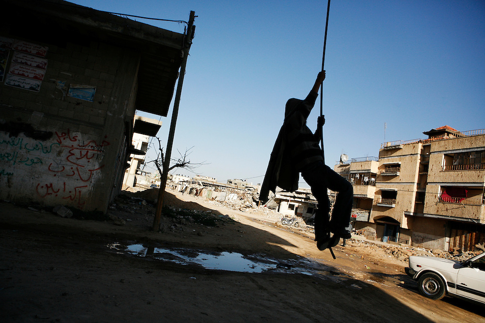 A boy swings from a downed electrical line hanging from a home in Rafah that was partially destroyed by Israel's 2008-09 invasion of Gaza.