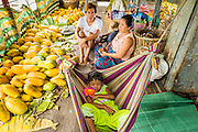 08 JUNE 2014 - YANGON, MYANMAR: A family on a river steamer sits amidst the papayas they're bringing to market. Yangon, Myanmar (Rangoon, Burma). Yangon, with a population of over five million, continues to be the country's largest city and the most important commercial center.      PHOTO BY JACK KURTZ