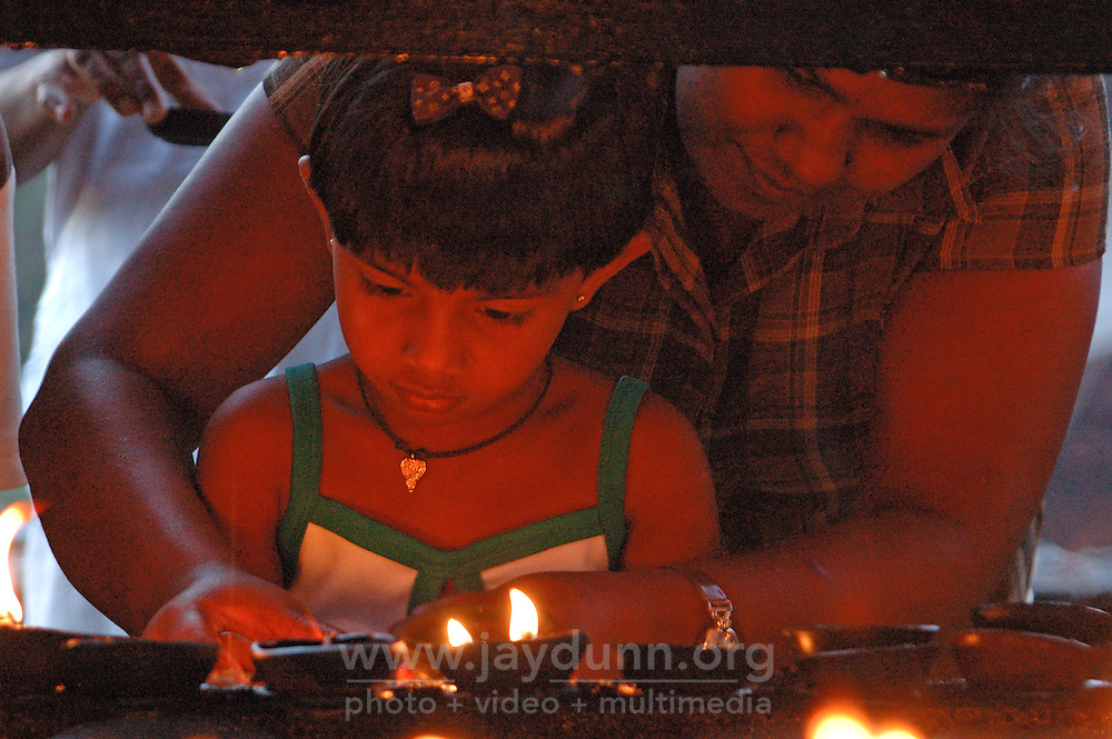 Sri Lanka, Kandy, 2006. A lesson in lamp lighting at Sri Dada Maligawa, the Temple of the Tooth. Spiritual center for the Sinhalese, Kandy was the last Sri Lankan city to fall to European colonizers.