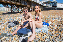 © Licensed to London News Pictures. 07/05/2018. Brighton, UK. 17 year old AMY COLLINS from Sandhurst and 16 year old FINN BOWER from Camberly spent the day on Brighton and Hove beach on the May Bank Holiday Monday as warm weather continues to hit the seaside resort. This weekend has been the hottest May Bank Holiday weekend on record. Photo credit: Hugo Michiels/LNP