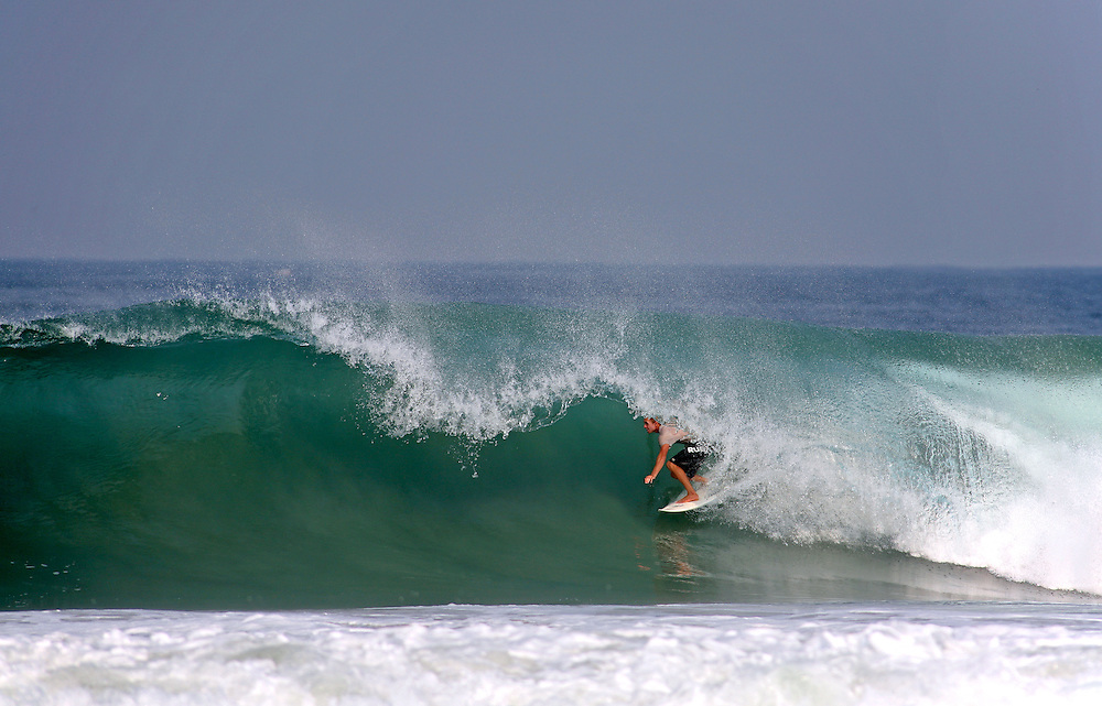 Surfer deep in a barrel on a wave that snapped his board. Puerto Escondido, Mexico