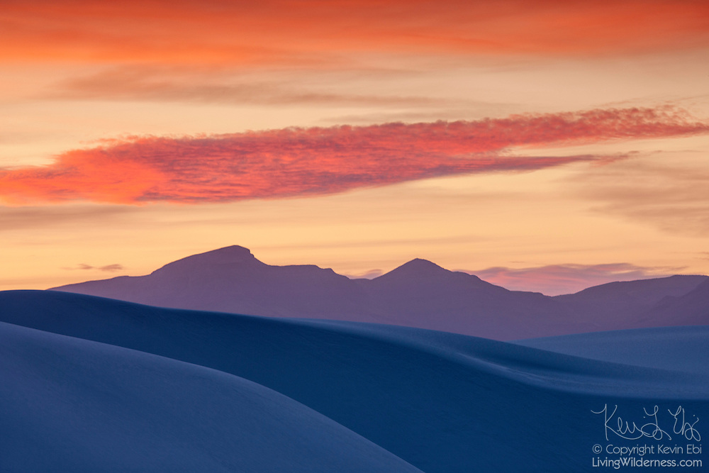 The white sand dunes of White Sand Dunes National Monument, New Mexico, appear blue and purple after sunset, reflecting the twilight sky. The white sand dunes are comprised of gypsum crystals, which is rarely found as sand because it is water-soluble. But the Tularosa Basin is surrounded by mountains and there is no direct outlet to the sea for any rain that falls there. Any water eventually drains through the ground leaving the gypsum behind in a crystalline form called selenite. White Sands National Monument is the largest gypsum dune field in the world.