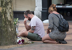© Licensed to London News Pictures. 21/04/2018. London, UK. A man who said he was a relative of the victim sits by flowers placed on the pavement opposite Morden Underground, south London where a man died following an assault. Police were called by the London Ambulance Service at 22:17hrs on Thursday, 19 April, after ambulance staff suspected that a man collapsed on London Road in Morden had been assaulted. The 32-year-old man was taken to a south London hospital in a critical condition. He died at 23:45hrs on Friday, 20 April. His next of kin have been informed. Photo credit: Peter Macdiarmid/LNP