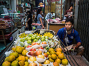 29 SEPTEMBER 2015 - BANGKOK, THAILAND:  A fruit vendor in a market near Saphan Lek. Street vendors and illegal market vendors in the Saphan Lek area will be removed in the next two weeks as a part of an urban renewal project coordinated by the Bangkok Metropolitan Administration. About 500 vendors along Damrongsathit Bridge, popularly known as Saphan Lek, have 15 days to relocate. Vendors who don't move will be evicted. Saphan Lek is just one of several markets and street vending areas being closed in Bangkok this year. The market is known for toy and replica guns, bootleg and pirated DVDs and CDs and electronic toys.   PHOTO BY JACK KURTZ