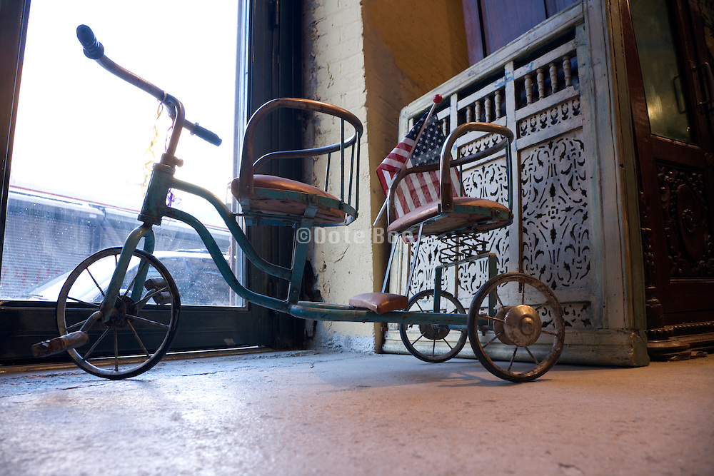 a antique twin seat tricycle with American flag