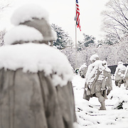 "The Korean War Memorial on the National Mall covered in a fresh blanket of snow. The bottom left corner of the frame is the back of one of the statues of soliders. The Korean War Veterans Memorial, unveiled in 1992, sits on the northwestern end of the National Mall, not far from the Lincoln Memorial. It consists of several elements designed by different people and groups. It has a triangular footprint with the main elements being ""The Column"" consisting of 19 stainless steel solders, each over 7 feet tall, and a reflective granite wall etched with the faces of thousands of Americans who lost their lives in the war. At one end of the triangle, behind the soldiers, is a grove of trees. At the other is a large American flag and a small Pool of Remembrance. Among the designers were Frank Gaylord (the soldiers) and Louis Nelson (the reflecting granite wall)."