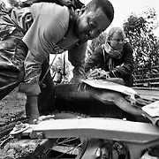 Digby and Steve pick up a grounded bike submerged in mud along the Ho Chi Minh Trail, Laos.