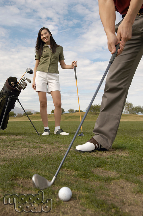 Woman Watching Man Ready to Hit Golf Ball