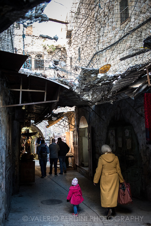 A woman walks with her daughter in a alley of Hebron old city market. The street is roofed with wire mesh to protect Palestinians from the Israeli living in the occupied buildings above. Settlers routinely throw stones, sewage, garbage, glass and eggs onto them.