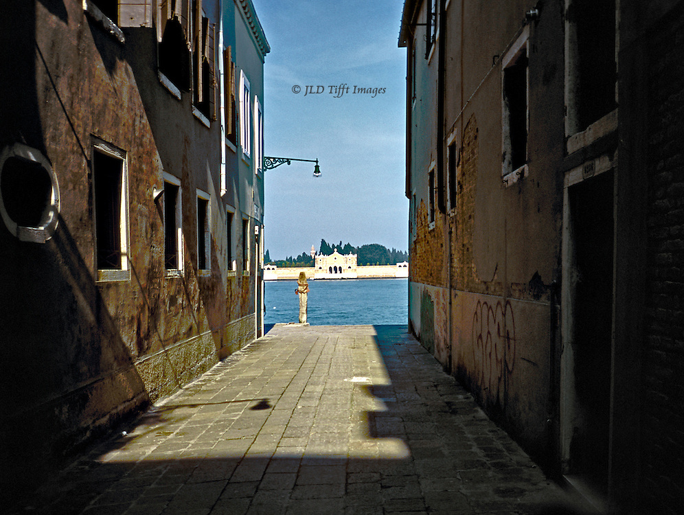View toward San Michele, cemetery island,down a calle near the Fondamente Nuove, Venice.  The gondola entrance to San Michele is visible in the distance across the laguna..