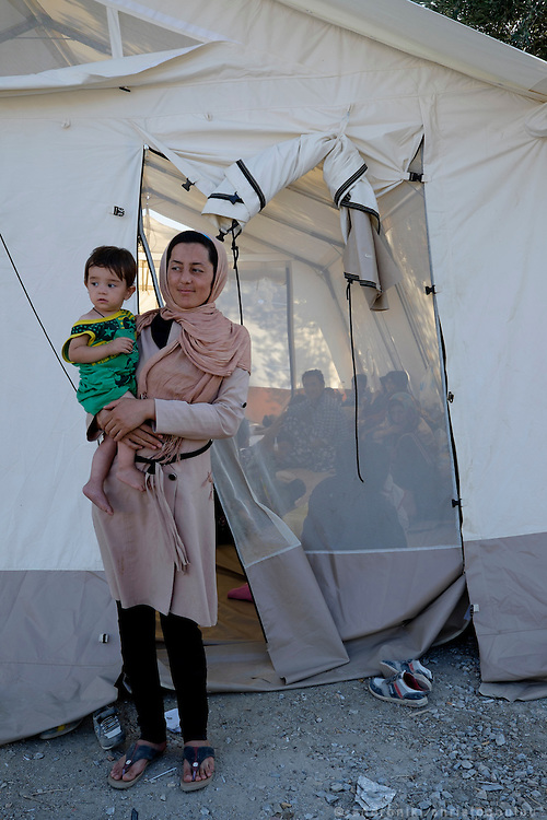 Saheb Zade Bashira with one of her their children in front of the tent where she is staying. <br /> They are from Kabul in Afghanistan where her husband had a street stall selling clothes. After an explosion near their home killed her nephew who was a policeman, they got scared and decided to leave the country. They want to go to Switzerland. <br /> Moria refugee camp is a bit further out of Mytilene city and it is divided in two sections. The inner part is well organised with buildings and police guarding it, and the outer part where mainly Afghan refugees live in tents and is purely guarded with chaotic situations, mainly during food distribution, frequently occur.
