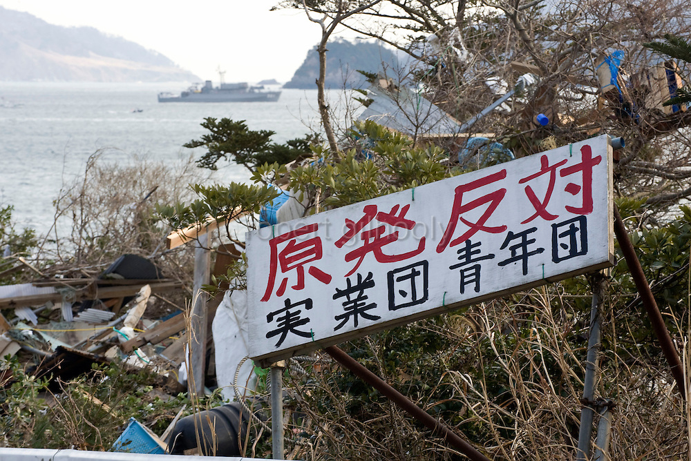 A sign expressing anti-nuclear energy sentiments  stands the entrance to the village of Yoriisohama in Ishinomaki, Japan on 19 March, 2011.  Meanwhile, in the bay behind a war ship can be seen. Photographer: Robert Gilhooly