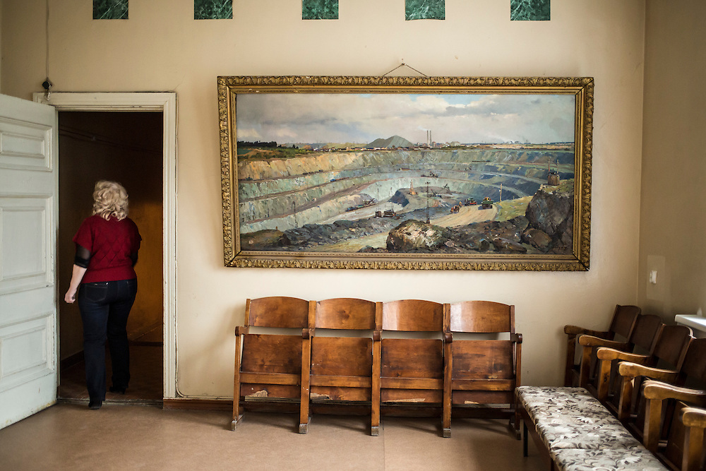 Ekaterina Khalitova, director of Asbest's arts center, walks past a painting of the town's enormous asbestos mine on Monday, November 11, 2013 in Asbest, Russia.