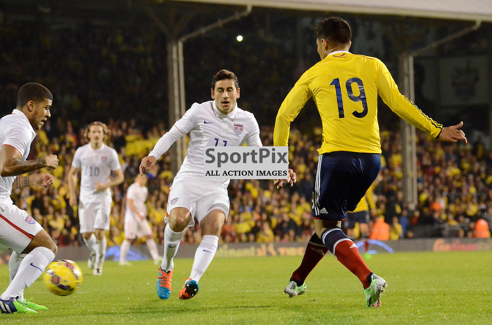 Colombias Teofilo Gutierrez puts the ball in the box despite pressure from USAs Alejandro Bedoya